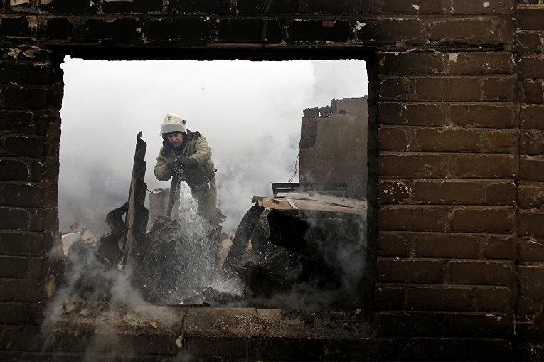 Пожарный заливает огонь в Авдеевке после обстрелов