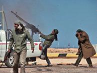 Боец оппозиции стреляет из пулемета в истребитель в городе Рас-Лануф
