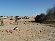 Горящий автомобиль после столкновений между ливийской армией и бойцами «Бригады обороны Бенгази» в Ливии