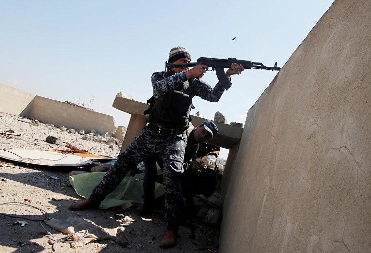Иракский полицейский обстреливает позиции боевиков исламского государства в Мосуле