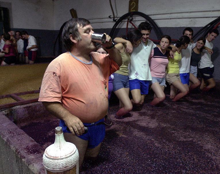 Процесс изготовления вина в традиционном каменном резервуаре в Португалии