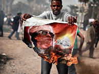 Житель Бенгази сжигает портрет Муамара Каддафи