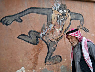 Прохожий проходит мимо рисунка на школьной стене в городе Суруч