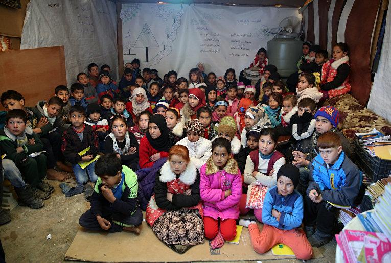 Сирийские беженцы слушают учителя в импровизированной школе в лагере для беженцев в городе Каб Элиас, Ливан