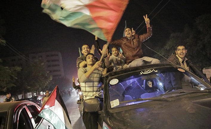 Палестнинцы празднуют вступление в силу соглашения о прекращении огня между Израилем и движением ХАМАС в городе Газа