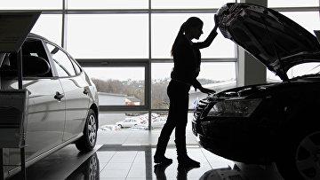 """Работа автосалона """"Лаура"""" в городе Посетительница осматривает автомобиль в автосалоне «Лаура» в Сочи"""