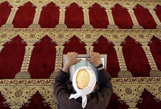 Палестинец читает Коран в мечети Аль-Акса, расположенной на территории Аль-Харам Аш-Шариф