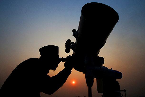 Улемы с помощью телескопа наблюдают за появлением новой луны, чтобы объявить начало священного месяца Рамадан