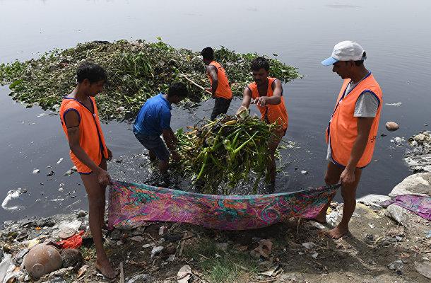 Рабочие, работающие по правительственной программе проводят работы по отчистке реки Ямуна в Нью-Дели