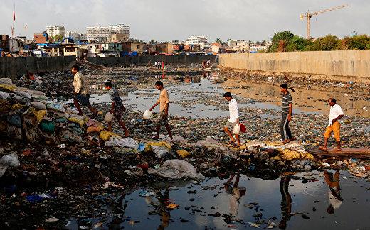 Жители индийского Мумбаи пересекают загрязненный канал в трущебах города