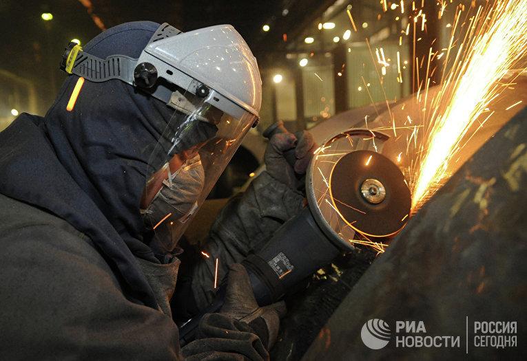 Рабочий во время обработки изделий на сталелитейном производстве