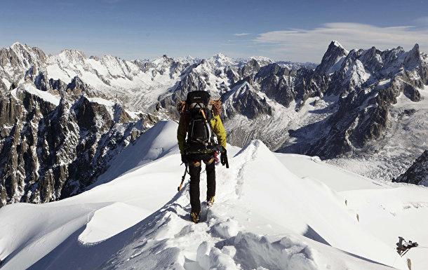 Альпинист на вершине горы Эгюий-дю-Миди во Франции