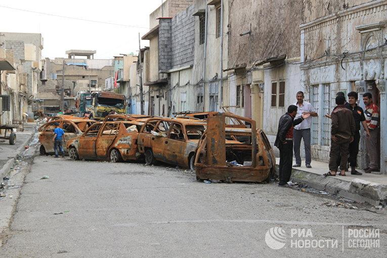 """Автомобили, сожженные боевиками """"Исламского государства (ИГ, организация запрещена в РФ), в западной части Мосула"""