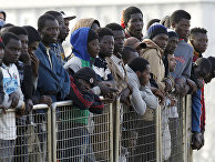 Мигранты из Ливии готовятся сойти на берег в Мессине, Сицилия