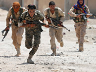 Курдские бойцы пробегают через улицу в Ракке 3 июля 2017