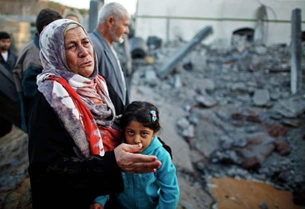 Жители сектора Газа у разрушенного дома