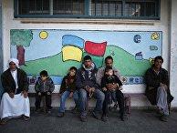 Палестинцы сидят у школы ООН в секторе Газа