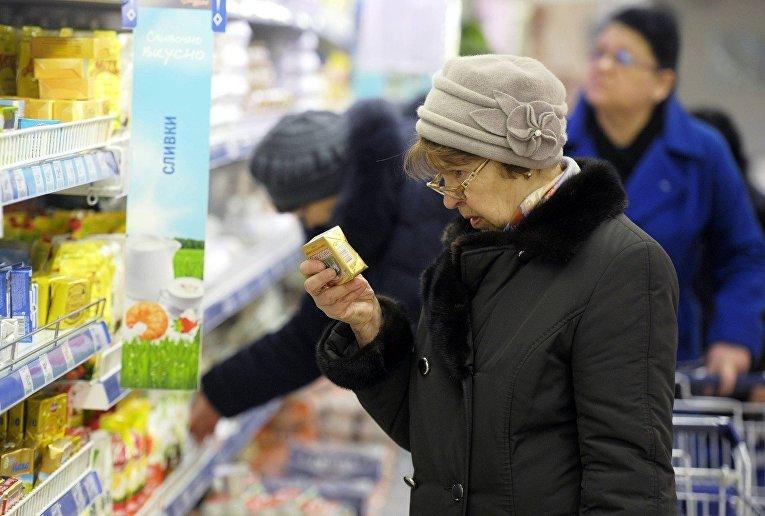 Женщина выбирает масло в магазине