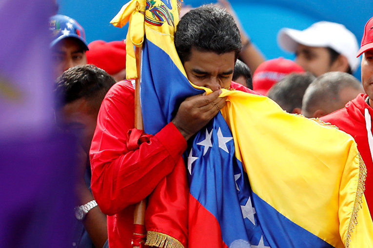 Президент Венесуэлы Николас Мадуро целует флаг страны в знак окончания предвыборной компании в Учередиельное собрание. 27 июля 2017