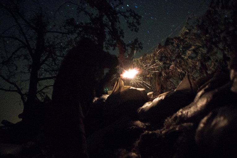 Украинский военнослужащий обстреливает позиции вооруженных сил ДНР в прифронтовом городе Красногоровка