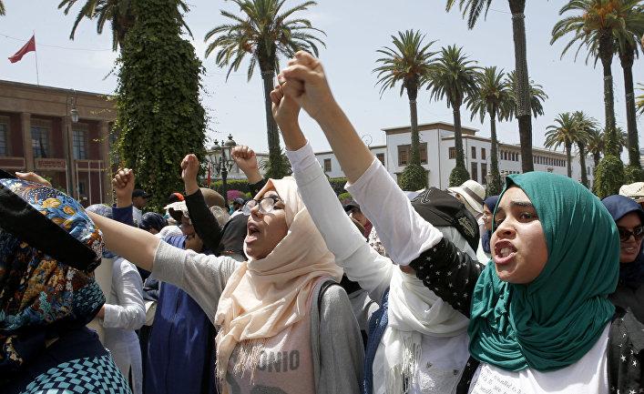 Женщины кричат перед марокканским парламентом во время демонстрации против коррупции в правительстве. 11 июня 2017 года