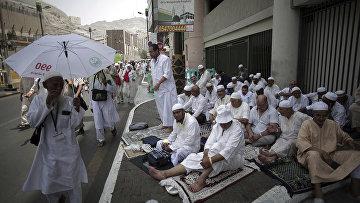 Паломники отдыхают в тени рядом с Великой мечетью накануне ежегодного паломничества в Мекке