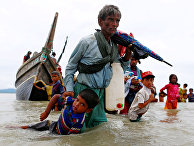 Мужчина из народности рохинджа вытаскивает ребенка из воды после пересечения границы Бангладеш-Мьянма через Бенгальский залив