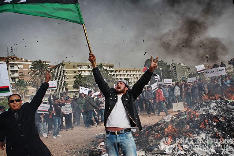 """Жители Бенгази сжигают портреты Муамара Каддафи, плакаты с его цитатами и """"Зеленую книгу"""" Каддафи"""