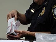 Полицейский открывает коробку с препаратом NARCAN, от передозировки наркотиками в полицейском участке в городе Глостер