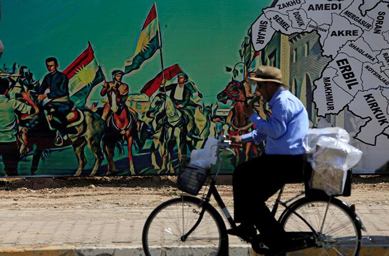 Мужчина проезжает мимо агитационного плаката, призывающего к референдуму в Эрбиле. 24 сентября 2017