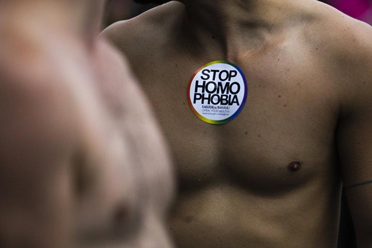 Мужчина с наклейкой, призывающей остановить гомофобию на ежегодном гей-параде в Берлине
