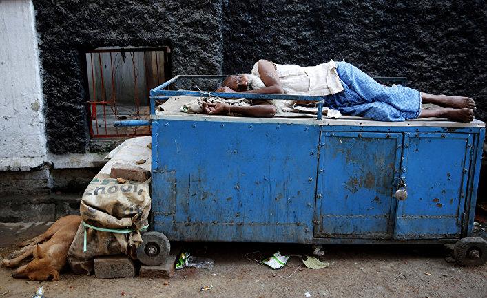 Спящий продавец чая на улице в Аллахабаде, Индия