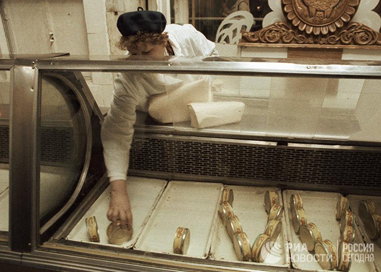 Продавщица продовольственного магазина выкладывает консервные банки на витрину