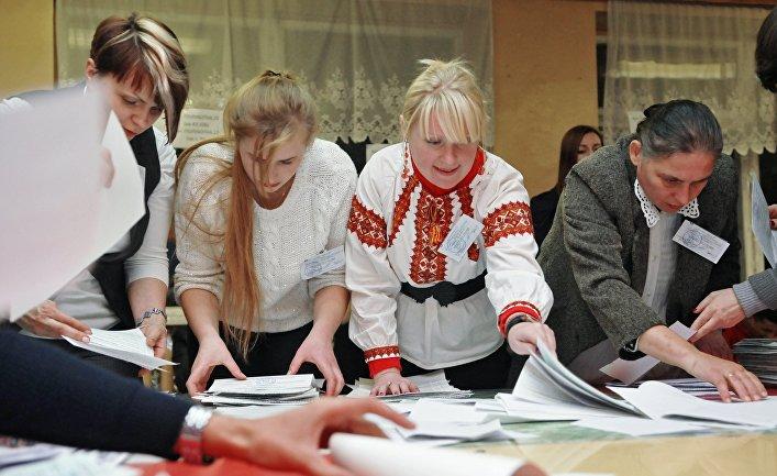 Сотрудники участковой избирательной комиссии на одном из избирательных участков Львова во время подсчета голосов на выборах