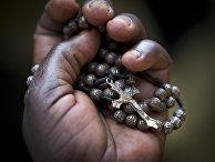 Женщина держит в руке распятие во время мессы в католическом храме в Кампалы в Уганде