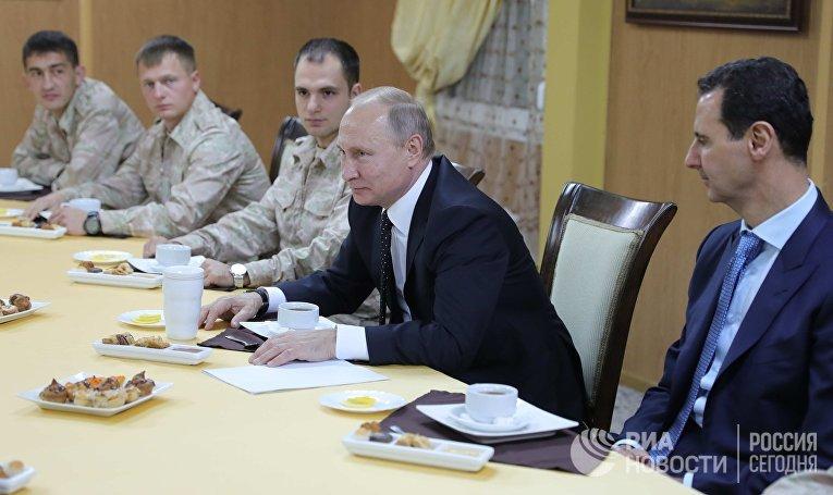 Президент РФ Владимир Путин и президент Сирийской Арабской Республики Башар Асад во время общения с военнослужащими авиабазы Хмеймим в Сирии