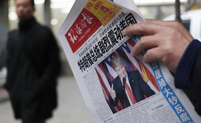 Мужчина читает газету с новостью об избрании Дональда Трампа президентом США. Пекин, 10 ноября 2016 года