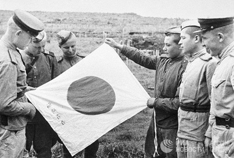 Советские воины рассматривают брошенный при отступлении японский флаг