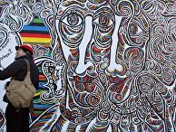 Пара фотографируется на фоне Берлинской стены