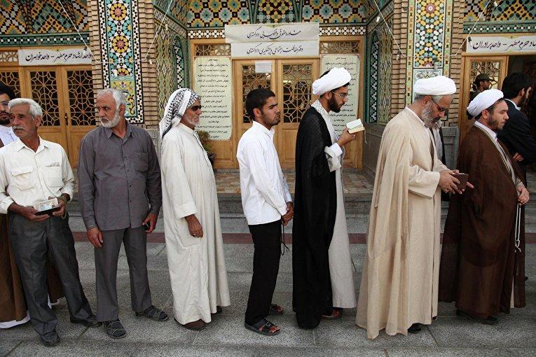 Мужчины стоят в очереди в мечети в Куме, чтобы проголосовать во время иранских президентских выборов