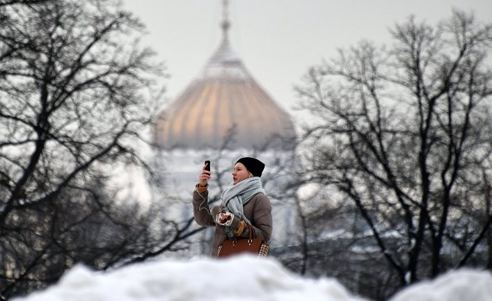 Девушка фотографируется в Александровском саду в Москве