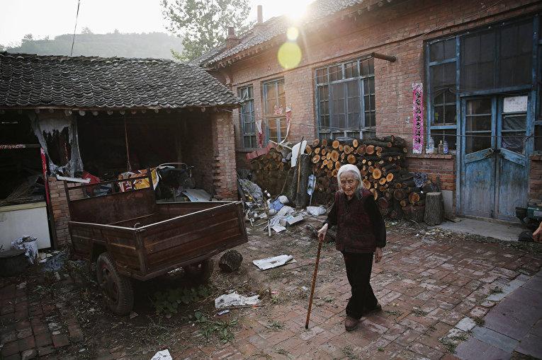 Цзюйсян Хао во дворе своего дома в городе Гучэн, провинция Шаньси