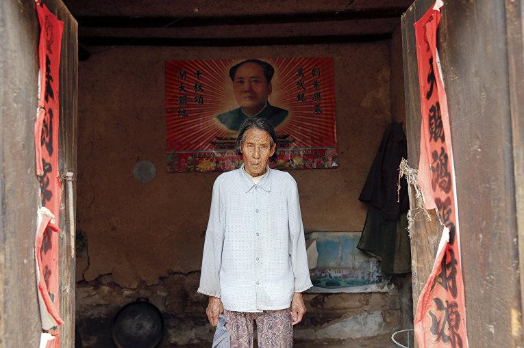 Жэнь Ланэ на фоне портрета Мао Цзэдуна в своем доме в городе Гучэн, провинция Шаньси