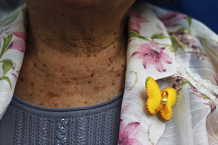 Бабочка на одежде бывшей «женщины для утещения» Кир Вон Окх