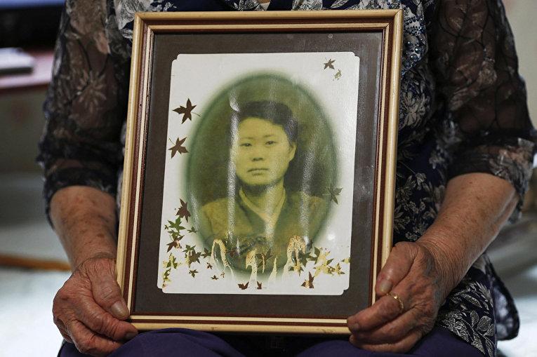 Ли Ок Сен показывает фотографию себя в 1947 году