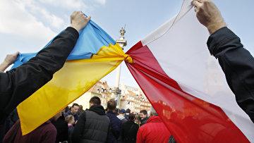 Люди держат связанные флаги Польши и Украины в Варшаве