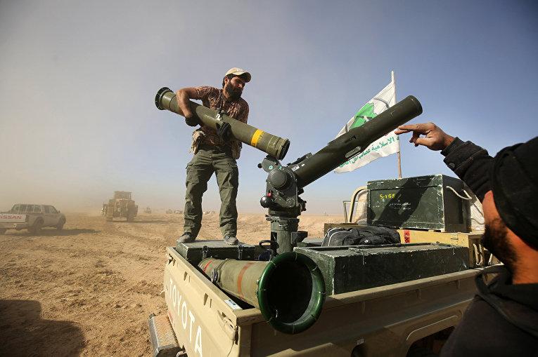 Боец из Хашед Аль-Шааби грузит ПТРК «ТОУ» в грузовик возле деревни Аль-Тофаха в Ираке