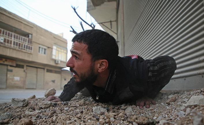Мужчина укрывается от авиаударов в пригороде Дамаска