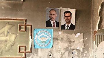 Портреты Владимира Путина и президента Сирии Башара Асада на крайнем КПП армии САР в лагере для Беженцев Вафидин в восточном пригороде Дамаска