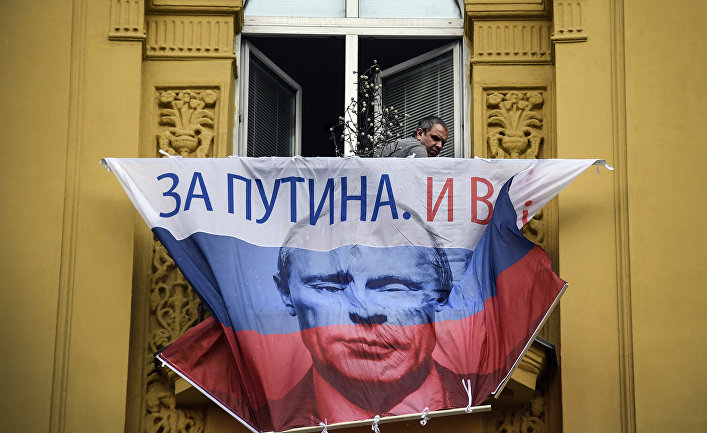 Флаг РФ с портретом Владимира Путина балконе квартиры в Москве